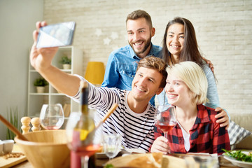 Portrait of four happy friends taking selfie at dinner table while celebrating festive occasion together
