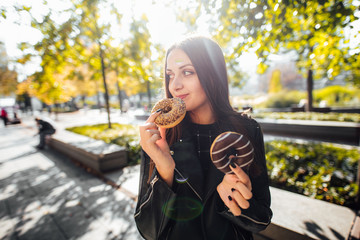 Young girl eat donut in park autumn background