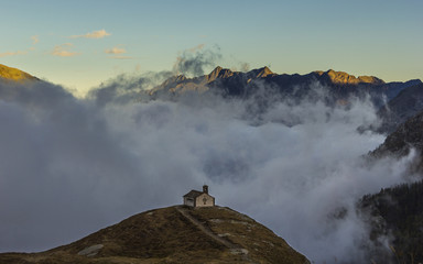 Orco Valley, Piedmont, Italy: Lonely church in the mountains, above the sea of fog.