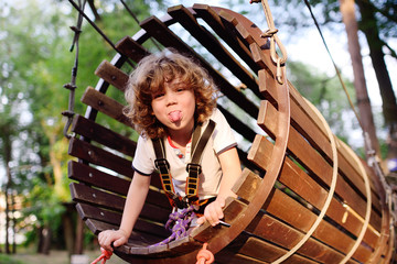 child - a cute, curly-haired boy in an amusement park climbing the rope road. Hyperactive child