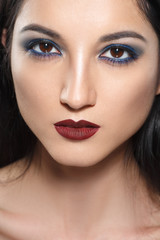 Fashion beauty portrait of a brunette girl with bright blue eye makeup.