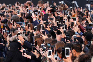 People use their smartphone to take photos on the Champs Elysees avenue during a public event in Paris