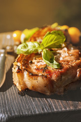 Grilled pork chop with basil leaf on wooden board
