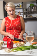 Woman cutting carrot with wine glass,noodle and paprika on foreground