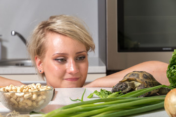 Young girl stares at tortoise eating salad