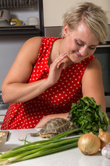 Girl smiles and observes tortoise who is eating roman salad