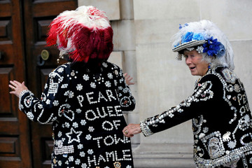 Women wear outfits decorated with buttons during the Pearly Kings and Queens Harvest Festival at the  St Martin-in-the-Fields church at the Trafalgar Square in London