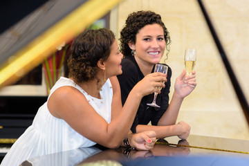 Two women drinking champagne, leaning on piano