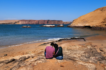 Young couple sitting on the ocean shore, sunny beach