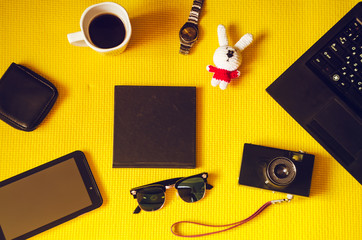 journey. objects on a yellow background. coffee, technology, clock, toy, notebook