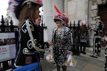 A woman wears an outfit decorated with buttons carries two baskets of fruits during the Pearly Kings and Queens Harvest Festival at the St Martin-in-the-Fields church at the Trafalgar Square in London