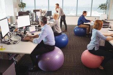 Business people sitting on exercise balls while working in
