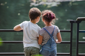 boy  and girl looking at green water