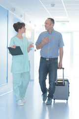 doctor and cured patient walkingin the hospital corridor