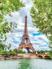 Classic view on Eiffel Tower through green poplar foliage over Seine river in Paris. Beautiful summer morning scenery. Vertical orientation. Eiffel Tower is famous travel destination in Europe.
