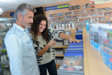 Shop assistant showing computer games to male customer