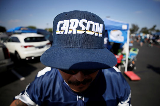 A fan wears a hat that says the city of Carson name in the same font as the Los Angeles Chargers logo as he tailgates outside StubHub Center where the Los Angeles Chargers are playing the Philadelphia Eagles in an NFL football game in Carson