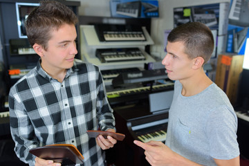 young men choosing music in a musical shop