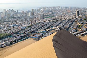 Ocean behind city behind sand dune
