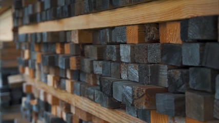 Background of the square ends of the wooden bars. Wood timber construction material for background and texture. close up. Stack of wooden bars. small depth of field. plywood boards on the furniture