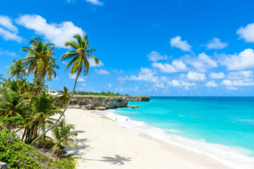 Deurstickers Strand Bottom Bay, Barbados - Paradise beach on the Caribbean island of Barbados. Tropical coast with palms hanging over turquoise sea. Panoramic photo of beautiful landscape.