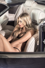 Sexy woman posing in luxury car in lingerie.
