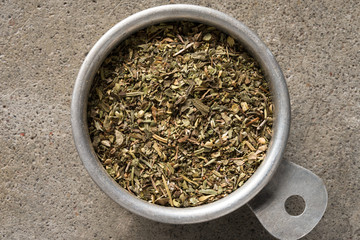 A vintage measuring cup of dried Italian seasoning