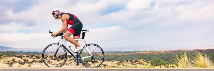 Triathlon biking man cycling on road bike in nature background banner. Cyclist triathlete riding bicycle in ironman competition. Panorama header crop for landscape copy space.