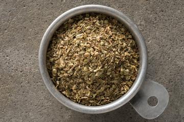 A vintage measuring cup of dried oregano