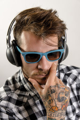 Handsome man with sunglasses and headphones posing