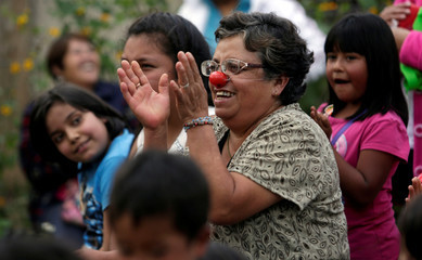 A woman wears a clown nose as she applauds during a show at a shelter for people who lost their homes in an earthquake in Ixtlahualtongo
