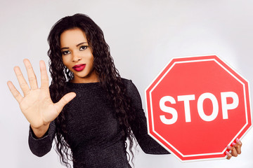 "A black girl holds a sign ""STOP"" in her hands. Girl hand shows stop sign."