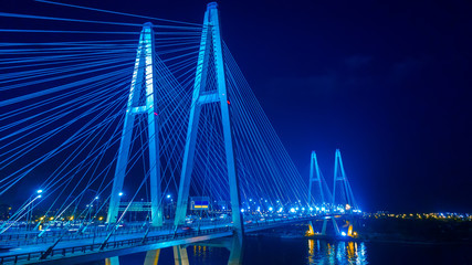 Night panorama to the cable-stayed bridge. Movement of cars on the bridge at night. The long bridge.