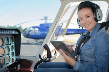 young woman with tablet in helicopter