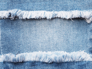 Edge frame of blue denim ripped over jeans texture background.