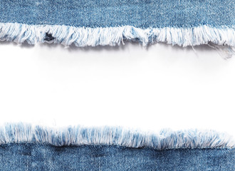 Edge frame of blue denim jeans ripped over white background.