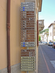 Assisi, Italy. A large number of small-scale signs showing the direction of the various monuments and main services of the city