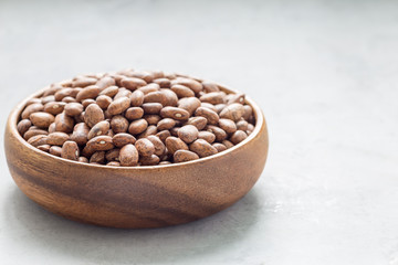 Uncooked dry pinto beans in wooden bowl, copy space, horizontal