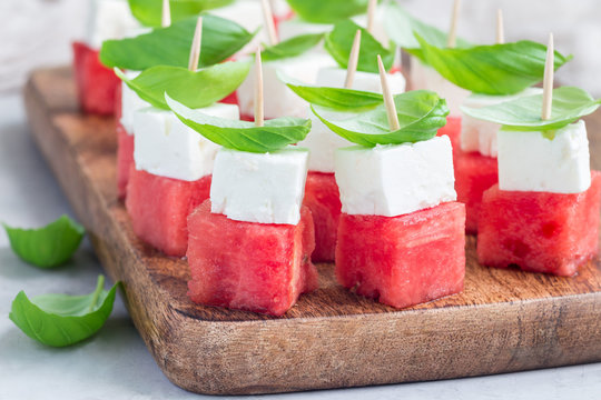 Watermelon salad or caprese with watermelon, feta and basil on wooden board, horizontal