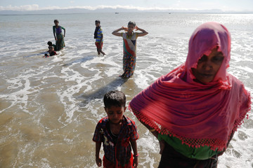 Rohingya refugees who just arrived by a wooden boat from Myanmar wait for the assistance of local community at the beach of Shah Porir Dwip