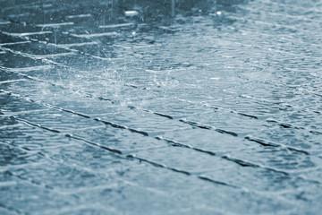 drops of heavy rain and water splash on sidewalk surface