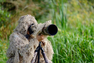 Camouflage wildlife photographer in the ghillie suit