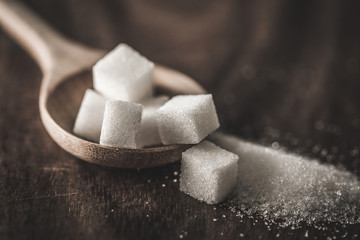 Close up the sugar cubes and cane in wooden spoon on the table ,retro color tone