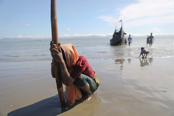 A woman collapses from exhaustion as Rohingya refugees arrive by a wooden boat from Myanmar to the shore of Shah Porir Dwip