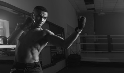 Afro american male boxer. Young man boxing workout in a fitness club. Muscular strong man on background boxing gym. Black and white photo.