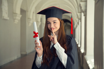 Happy woman holds a finger on her mouth a secret on her graduation day University. Education and people.