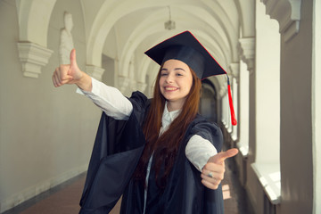 Happy woman on her graduation day University. Thumbs up woman.