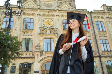 Happy graduate. Woman student in bachelor gown with diploma.