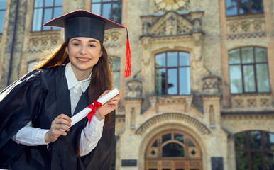 Happy woman student in bachelor gown with diploma.
