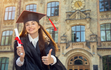 Happy woman in bachelor gown with diploma. Woman student showing thumbs up.